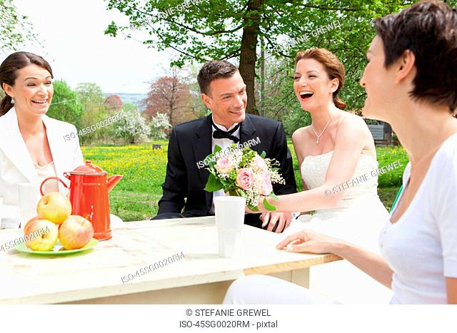 Newlywed couple at table with friends