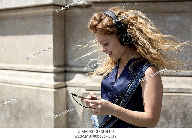 Smiling young woman with headphones looking at her smartphone