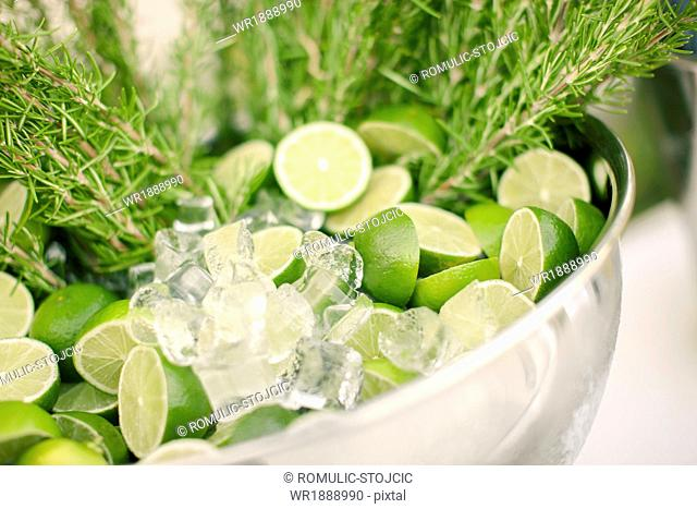 Lime slices and ice cubes in ice bucket