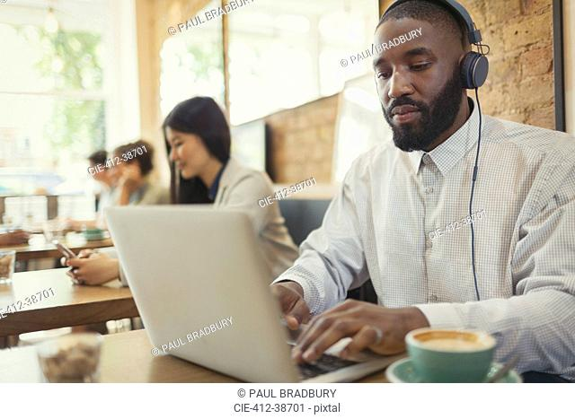 Young man with headphones using laptop and drinking coffee at cafe table