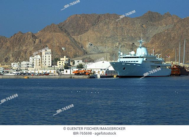 Large motor yacht in the harbour with rocky mountains rising at back, Muttrah, Muscat, Sultanate of Oman, Middle East