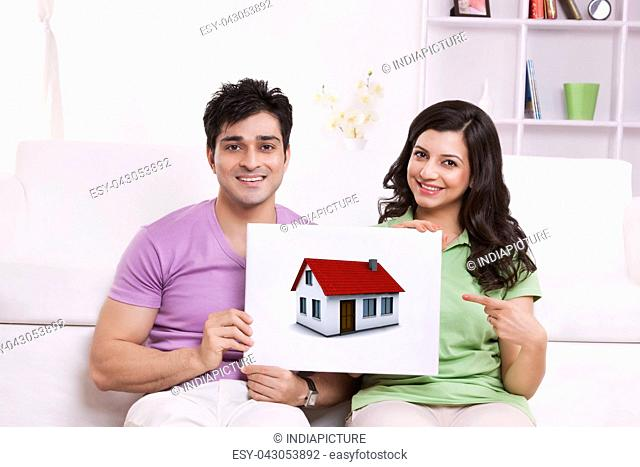Portrait of couple pointing to picture of house