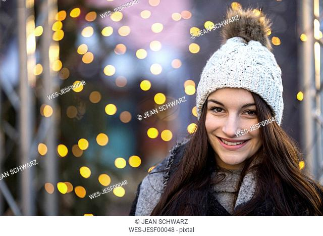 Portrait of smiling young woman wearing bobble hat at Christmas time