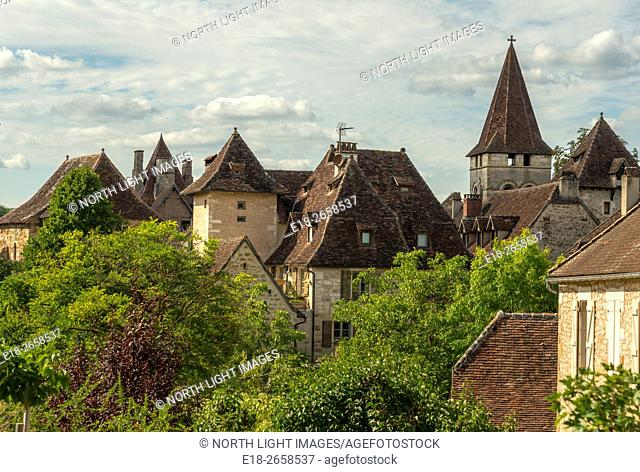 France, Midi-Pyrénées, Carrenac. Rooftops and leafy trees in quaint village in the Dordogne Valley. Carenac is officially classified as one of the most...