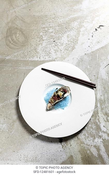 A grilled oyster on blue salt (Asia)