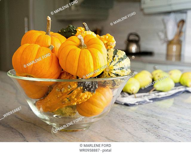 Bowl of gourds and mini pumpkins on a kitchen counter in a modern fitted kitchen. Pears on a chopping board