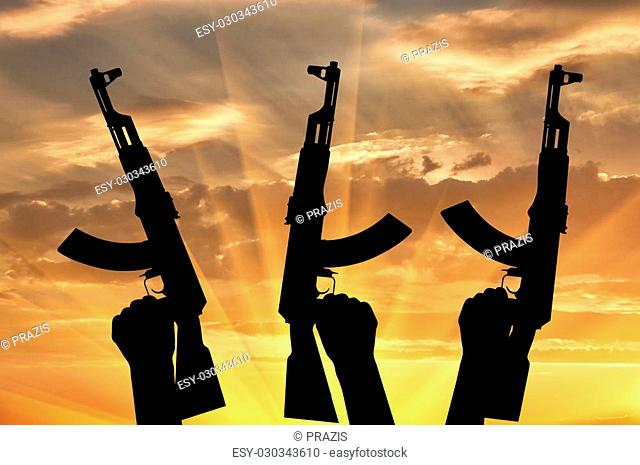 Terrorists concept. Weapons in the hands of terrorists, on the sunset background