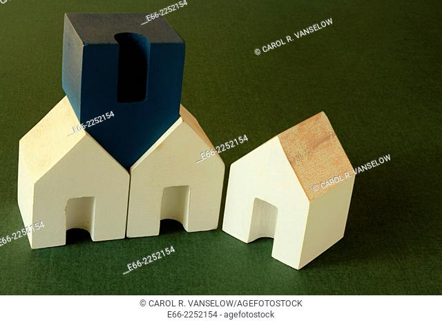 Still life with wooden block houses (3 white ones and one blue one) on dark green (the color of American money) background