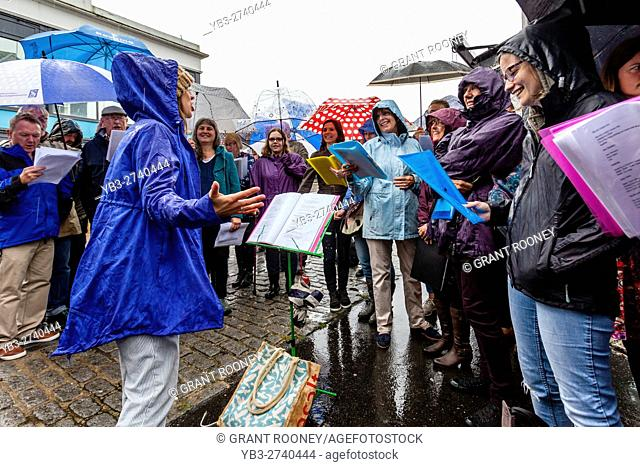 A Community Choir Performing In The Rain, The High Street, Lewes, Sussex, UK