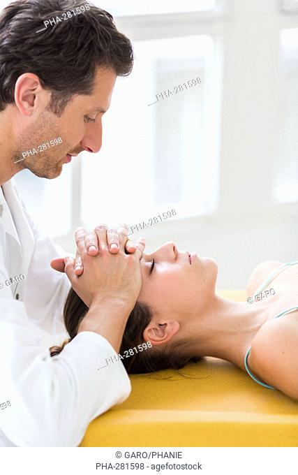 Woman's head being manipulated by an osteopath