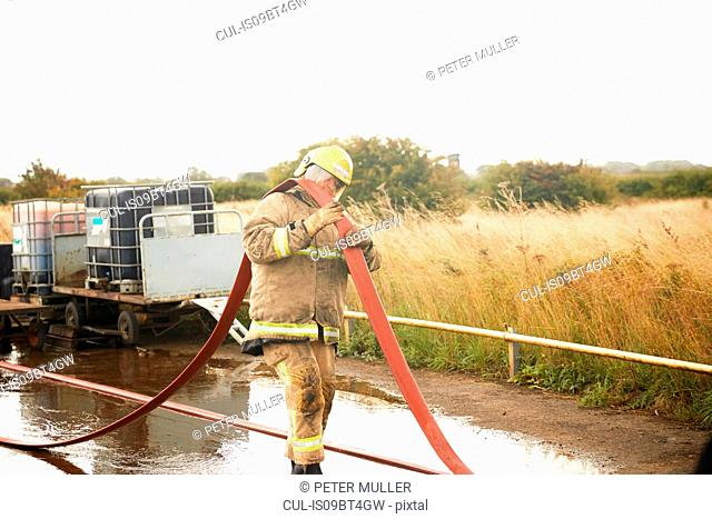 Firemen training, fireman carrying fire hose over his shoulder at training facility