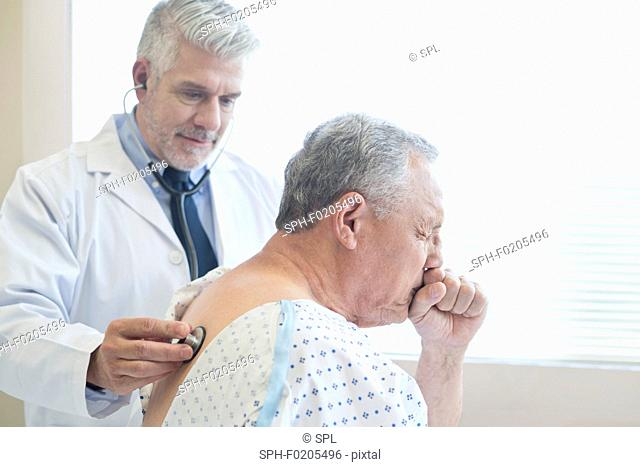 Male doctor examining patient in hospital gown