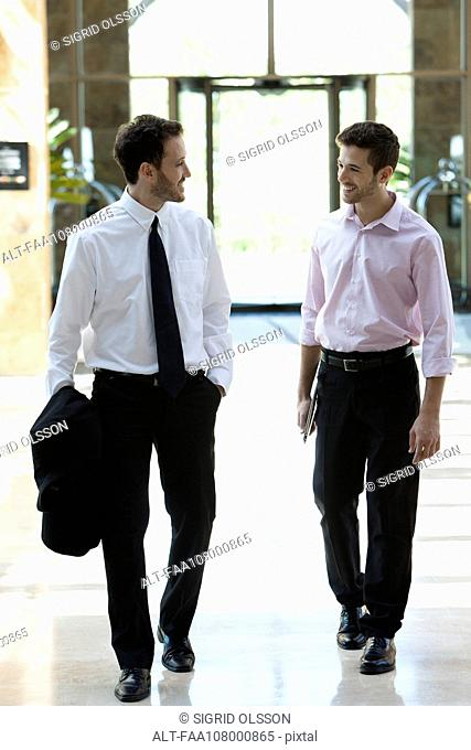 Business colleagues chatting while walking together