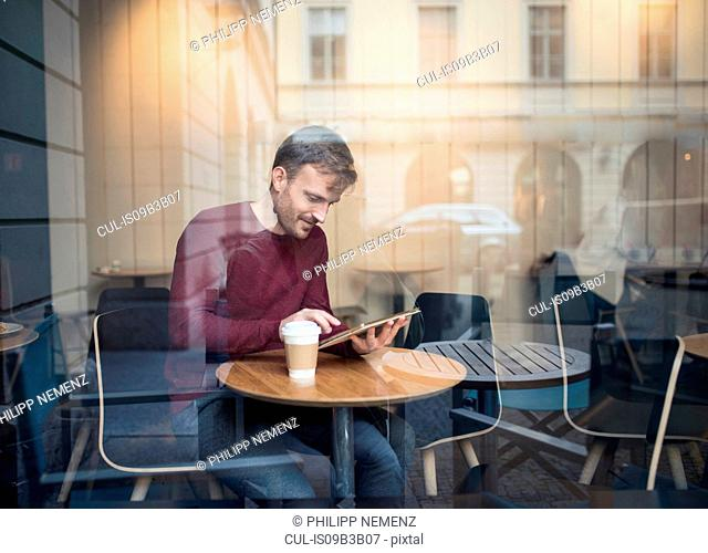 Window view of man using digital tablet touchscreen in cafe