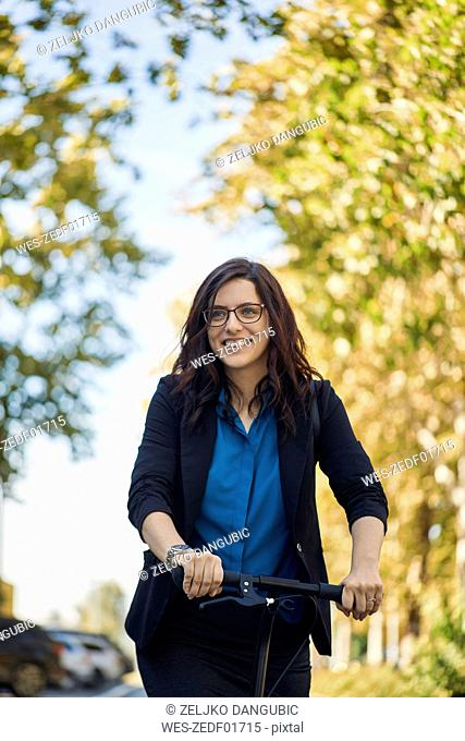 Portrait of smiling businesswoman with scooter