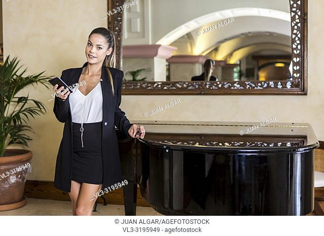 Modern beautiful woman in suit holding smartphone and standing in room with piano and mirror on wall