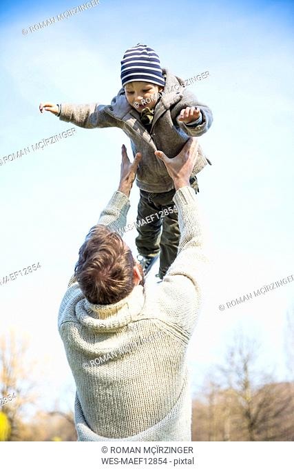 Father throwing happy boy in the air under blue sky