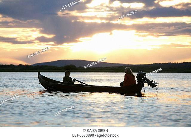 Couple rowing on river on summer night  Midnight sun  Finland