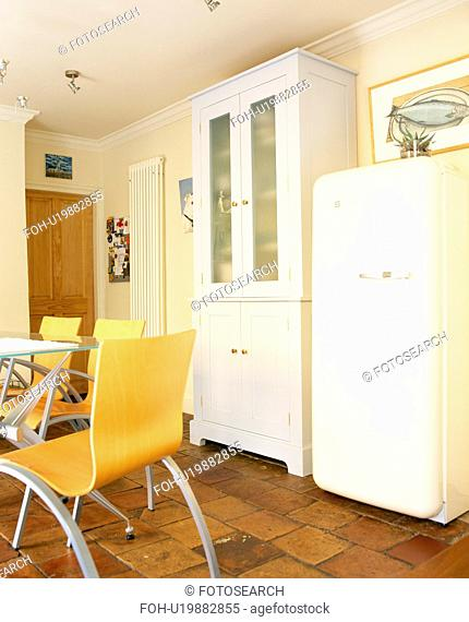 Large white fifties-style refrigerator beside white cupboard in traditional country kitchen with modern chairs