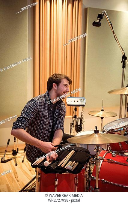 Smiling drummer sitting near drum set