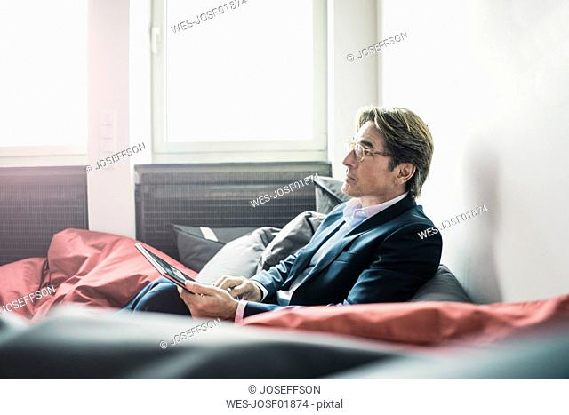 Businessman using tablet at lounge area in office