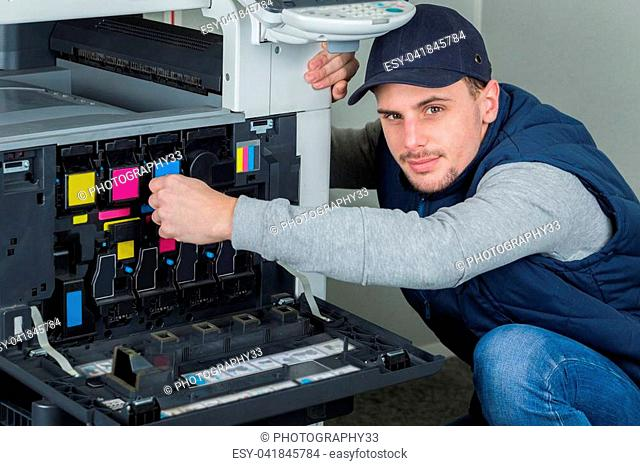 young male technician repairing digital photocopier printer machine