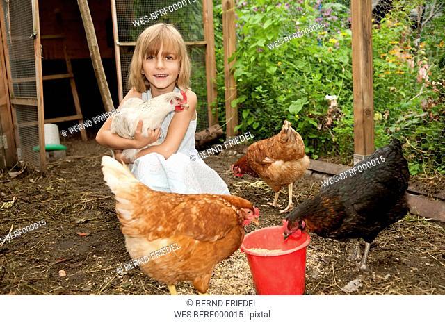 Germany, Brandenburg, Girl on hen farm