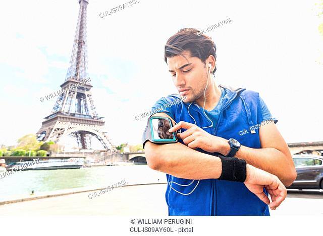 Young man exercising outdoors, adjusting smartphone on arm, Eiffel Tower in background