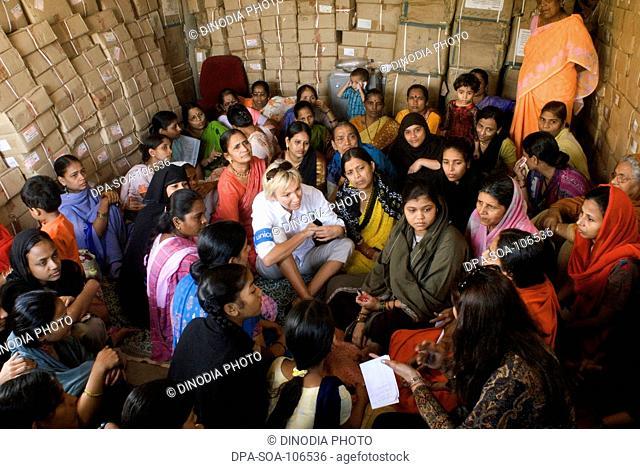 Sabine Christiansen in conversation with women at Amrae an NGO at Nehru Nagar ; Golibar Slum ;Santacruz ;Bombay Mumbai ; Maharashtra ; India NO MR