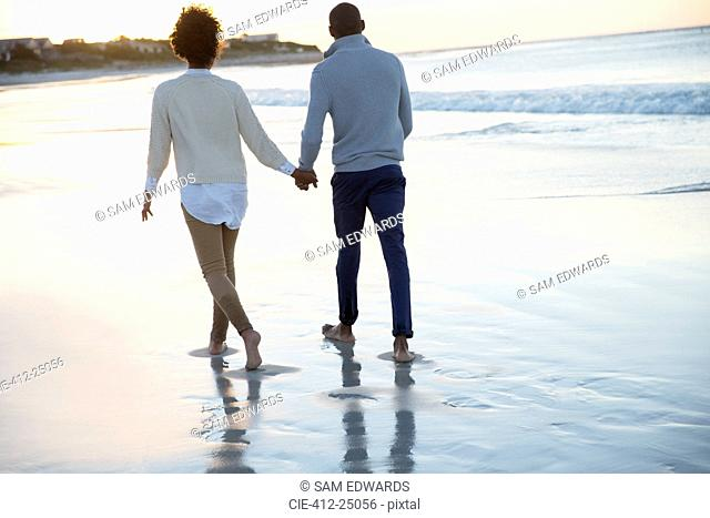 Young couple holding hands and walking on beach