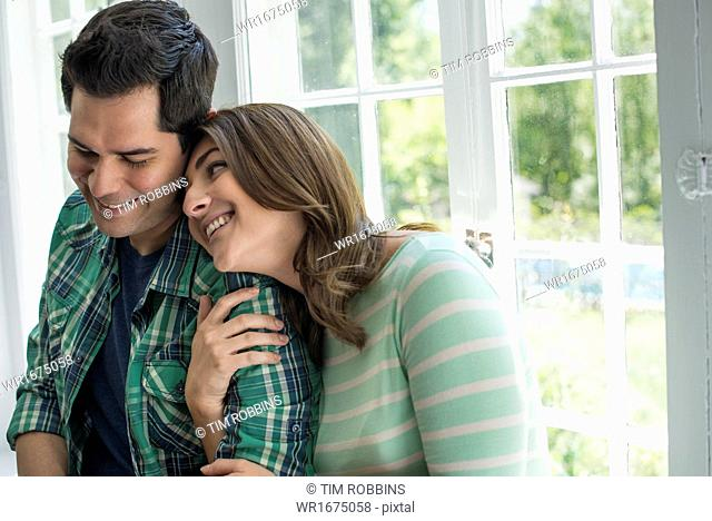 Couple embracing by a window