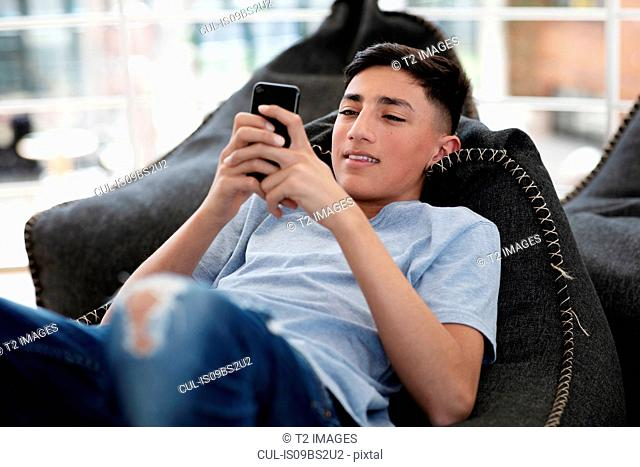 Teenage boy lying on beanbag and reading text message on cellphone