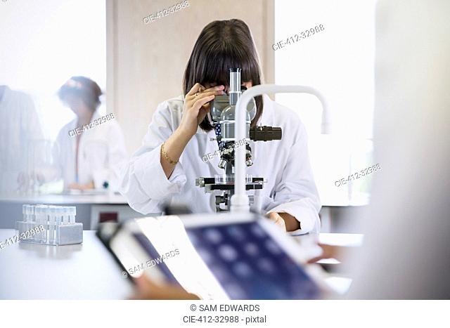 Female college student using microscope in science laboratory classroom