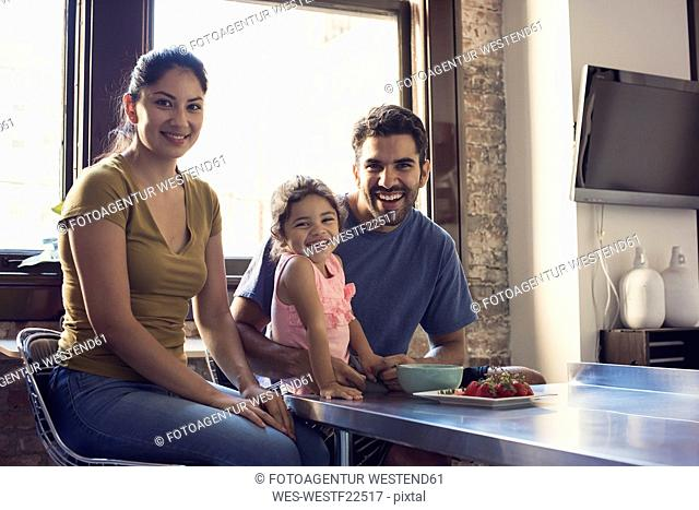 Familiy sitting in kitchen, looking at camera