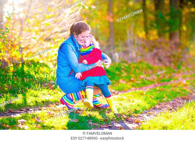 Happy young mother and her adorable toddler daughter, cute curly little girl in a colorful dress and warm coat, playing together in a beautiful autumn park...