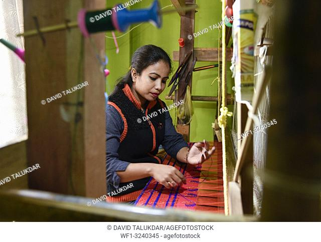 Nagaon, Assam, India. February 11, 2019. Women weaving Assamese silk costumes in a traditional method in a manufacturing unit at Nagaon, Assam