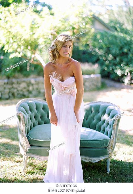 Bride wearing wedding dress near sofa in backyard