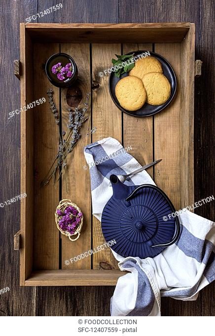 Green tea in a pot and cup, edible flowers, herbs and biscuits in a wooden box