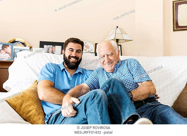 Portrait of adult grandson and his grandfather sitting on the couch at home tickling each other