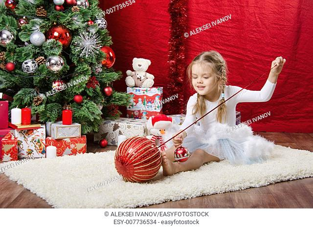 Girl sitting on a rug in the Christmas tree with Christmas tree balls