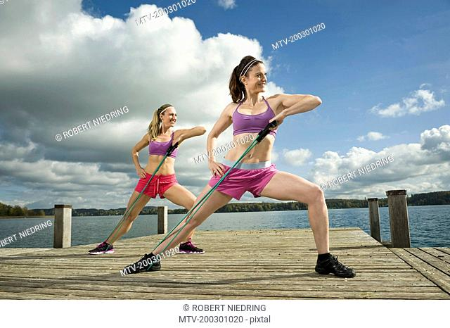 Women exercising on jetty with resistance band, Woerthsee, Bavaria, Germany