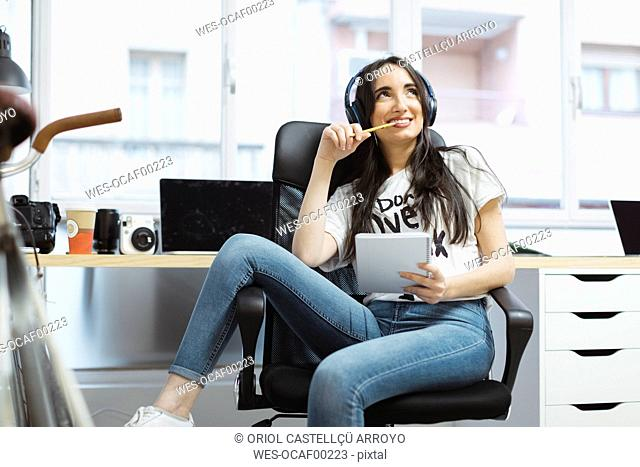 Casual young woman with notepad and headphones in coworking space