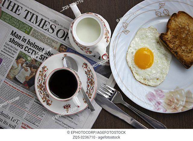 Omelette with roasted bread served on plate as morning breakfast along with news paper, Pune, India