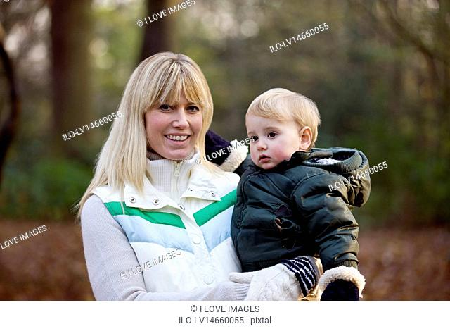 A mother holding her son in the park