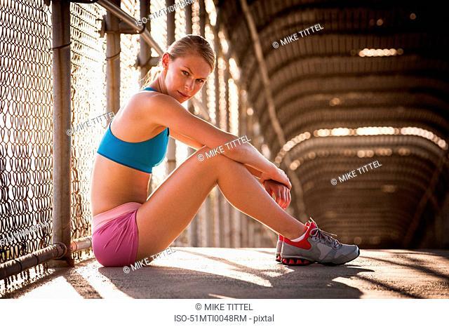 Woman sitting on urban footbridge