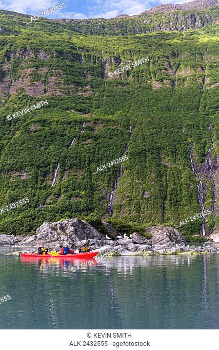 Couple sea kayaking in a tandem kayak in Shoup Bay State Marine Park, Prince William Sound, Southcentral Alaska