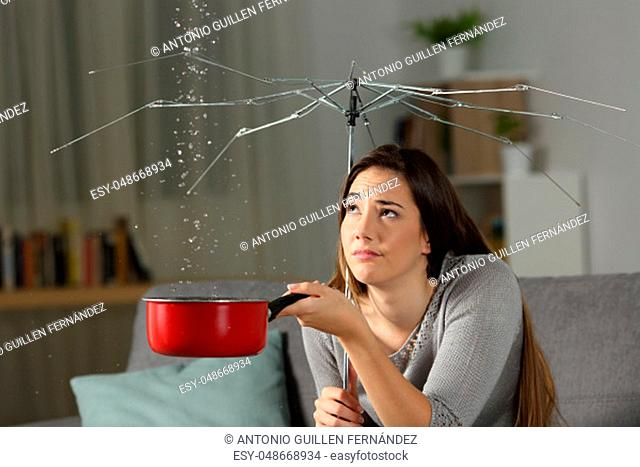 Woman suffering water leaks at home with a broken umbrella. Bad insurance concept