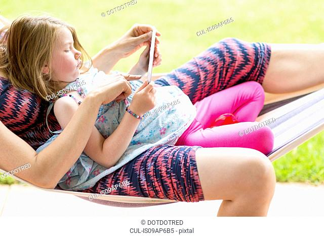 Mother and daughter on hammock, using digital tablet