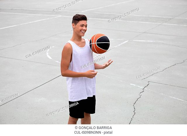 Male teenage basketball player on basketball court throwing and catching ball