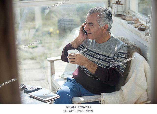 Senior man drinking coffee and talking on cell phone on sun porch